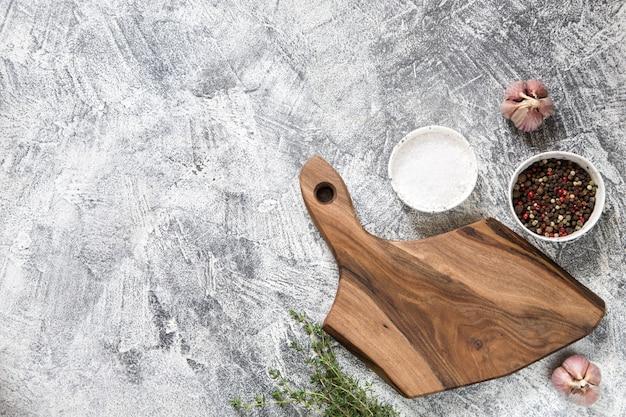 Planche à découper avec des ingrédients sur fond de béton gris