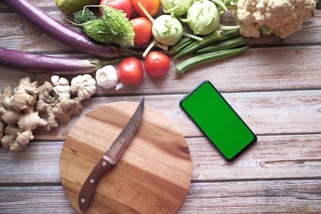 Planche à découper de légumes frais et téléphone intelligent sur table