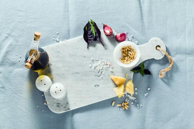 Planche à découper en marbre et épices sur une nappe bleu lin. huile d'olive, pignons de pin et basilic. copie espace
