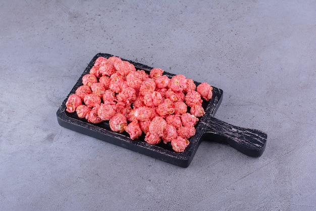 Planche à découper noire de boules de pop-corn roses sur la surface de la pierre