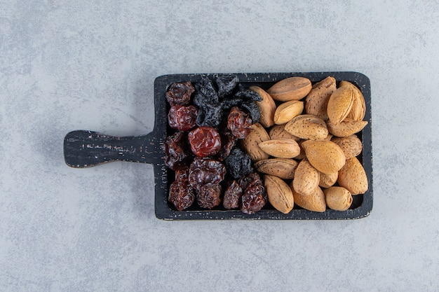 Planche à découper noire pleine de dattes sèches et de noix sur fond de pierre.