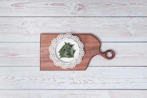 Planche à découper avec plaque d'ornement et feuilles vertes