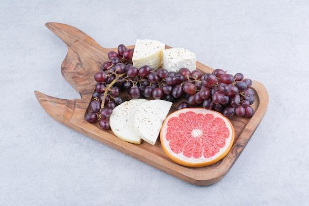 Une planche à découper pleine de fromage, tranche de pamplemousse et raisins. photo de haute qualité
