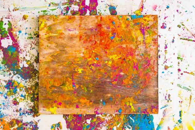 Planche à découper près de taches de différentes couleurs vives et sèches