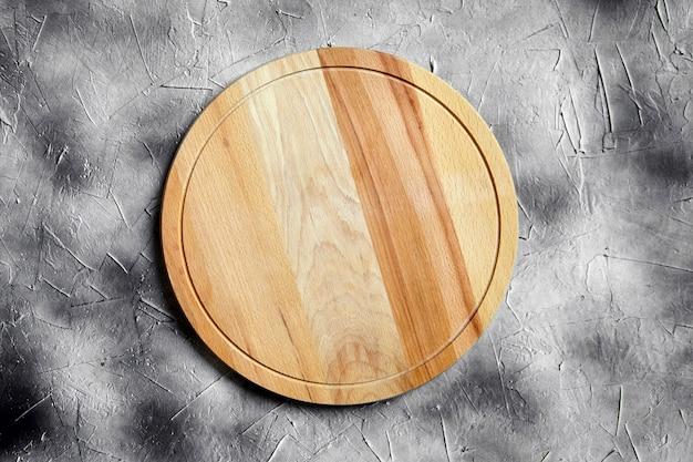 Planche à découper ronde vide en bois de hêtre sur table en pierre, fond gris, vue du dessus