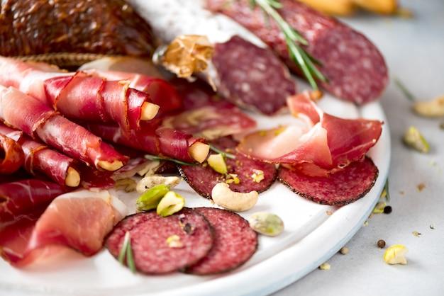 Planche à découper avec salami, prosciutto, jambon, côtelettes de porc