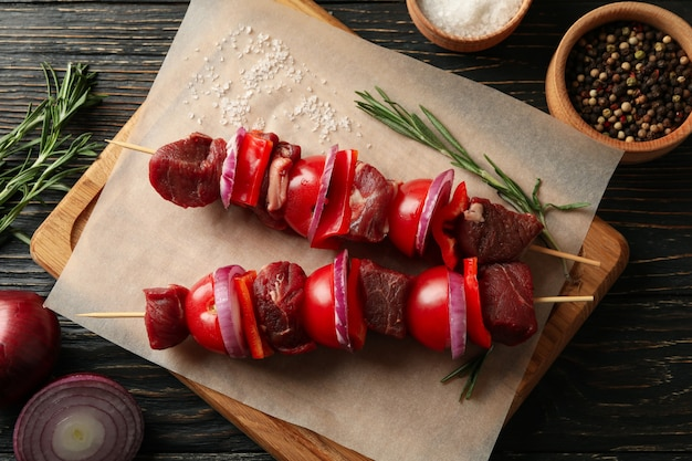 Planche à découper avec shish kebab cru sur bois
