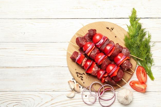 Planche à découper avec shish kebab et ingrédients sur bois