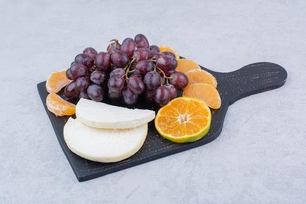 Une planche à découper sombre avec du fromage en tranches et des fruits. photo de haute qualité