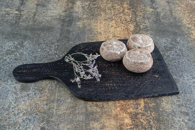 Une planche à découper sombre avec du pain d'épices et des fleurs fanées