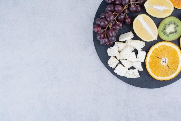 Une planche à découper sombre de fruits frais et de fromage blanc tranché. photo de haute qualité