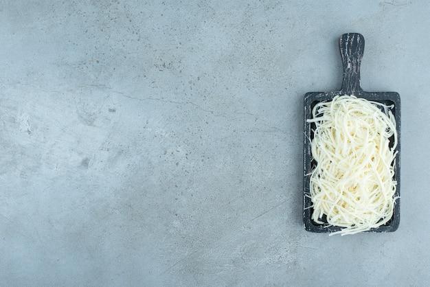 Une planche à découper sombre pleine de fromage sur fond bleu. photo de haute qualité