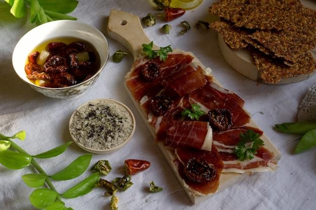 Une planche à découper avec des tapas traditionnelles avec de la viande espagnole, tomates séchées au soleil