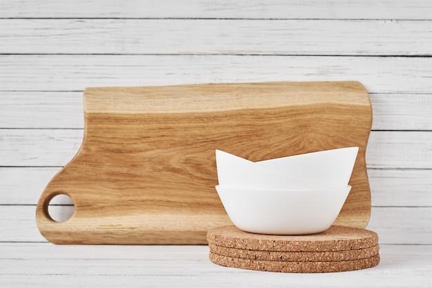 Planche à découper et tasse en céramique blanche sur blanc