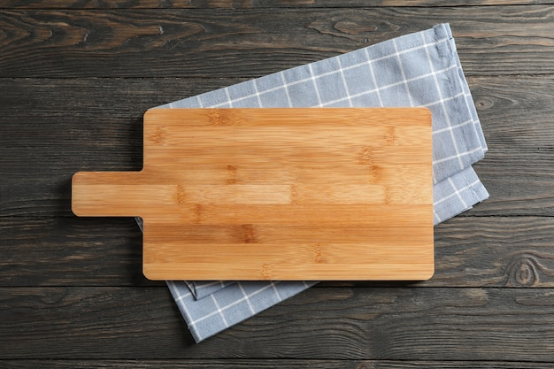 Planche à découper avec un torchon sur fond en bois, espace pour le texte