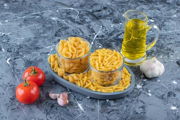 Une planche de deux types de macaronis crus avec des légumes et de l'huile sur un fond de marbre.