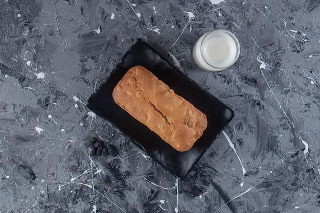 Une planche avec du pain aux raisins frais cuit au four placé sur une surface en marbre.