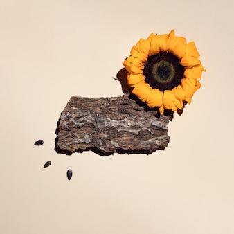 Une planche faite d'écorce d'arbre, de tournesol et de graines. avec une ombre serrée sur une surface claire