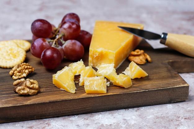 Planche à fromage avec fromage à pâte dure, couteau à fromage, verre de vin rouge, raisin sur une surface en béton brun