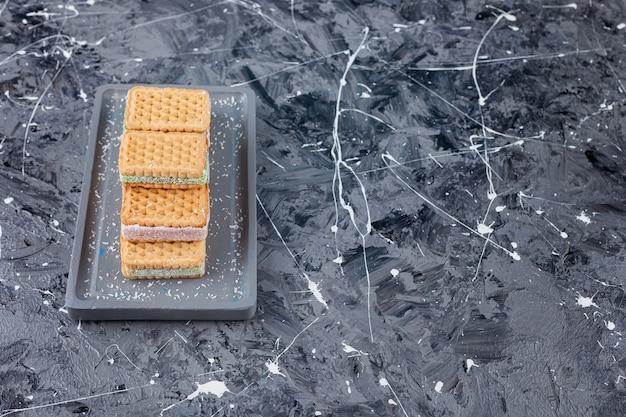 Une planche grise de gaufres sucrées posée sur un marbre.