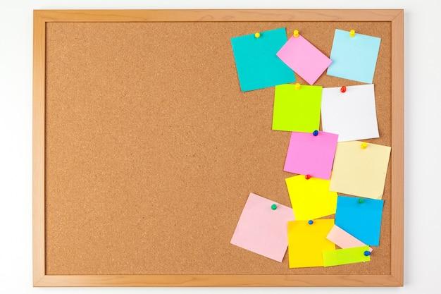 Planche de liège avec plusieurs notes vierges colorées avec des épingles