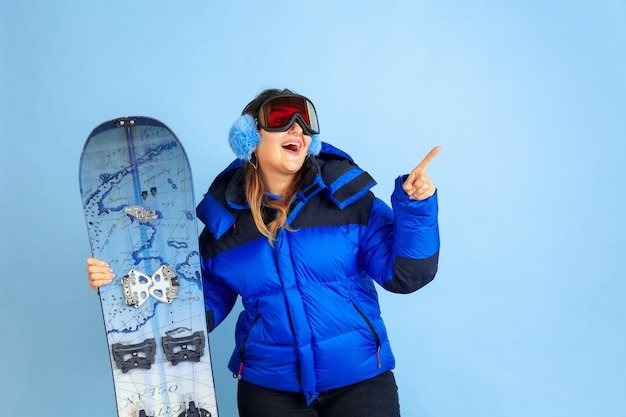 Planche a neige. portrait de femme caucasienne sur fond bleu studio. beau modèle féminin dans des vêtements chauds. concept d'émotions, expression faciale, ventes, publicité. humeur hivernale, période de noël, vacances.