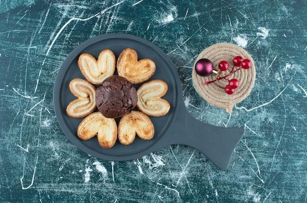 Une planche noire avec muffin au chocolat et biscuits. photo de haute qualité