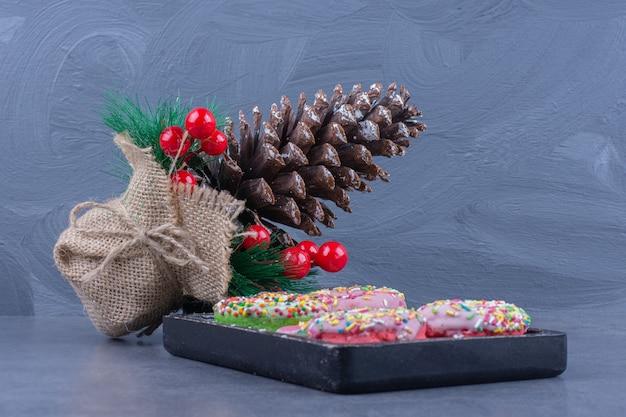 Une planche noire pleine de beignets avec des bonbons à la gelée sucrée
