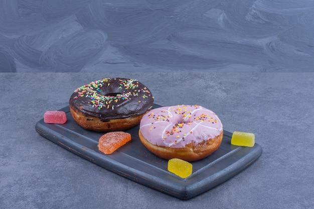 Une planche noire pleine de beignets et de bonbons à la gelée sucrée