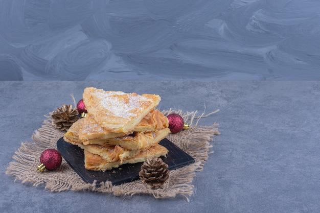 Une planche noire pleine de délicieuse tarte avec du sucre en poudre sur un sac