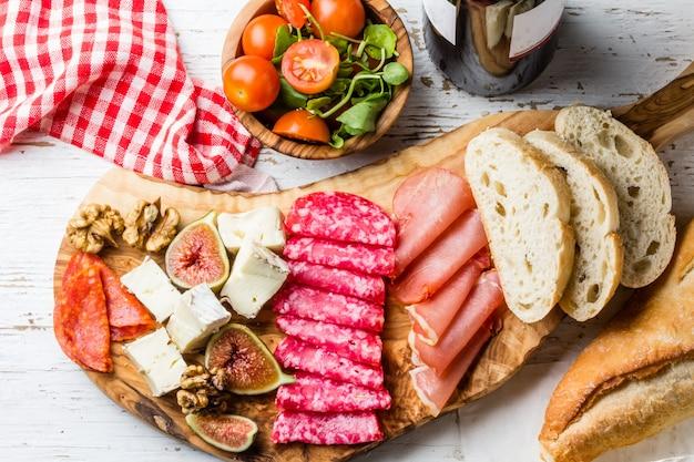 Planche d'olive avec salami, jambon serrano, fromage, noix et pain ciabatta