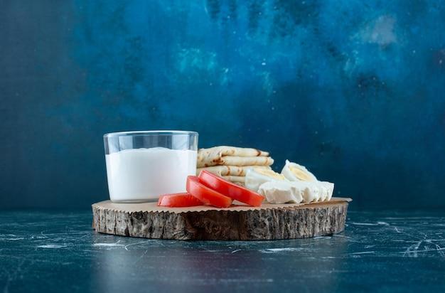 Planche de petit-déjeuner avec salade de légumes et une tasse de crème sure.