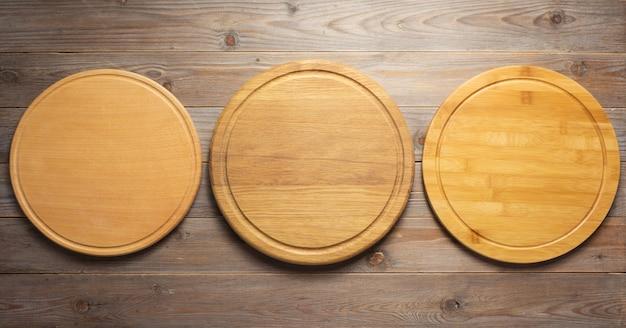 Planche à pizza à découper sur fond de planche de table en bois, vue de dessus