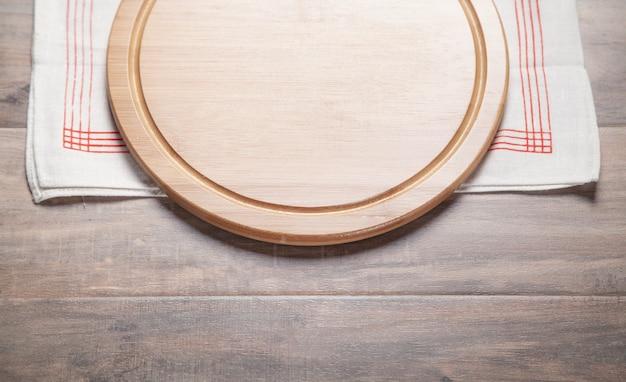 Planche à pizza vide et nappe en tissu sur le fond en bois.
