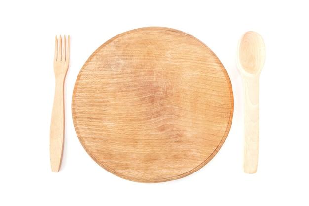 Planche ronde en bois et cuillère avec fourchette isolé sur fond blanc. vue d'en-haut.
