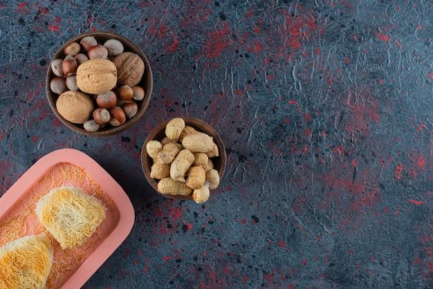 Une planche rose avec des délices turcs et des noix saines sur un fond sombre.