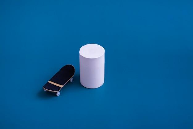Planche à roulettes de doigt sur un fond bleu, près du podium blanc. touche anti-stress pour enfants et adultes. divertissement