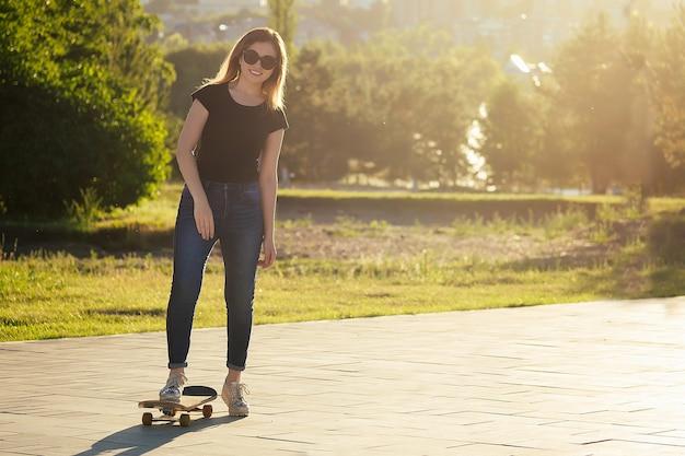 Planche à roulettes longboard close-up dans les mains d'une jeune femme en jeans et un t-shirt noir dans le parc.