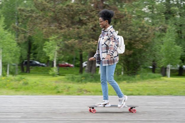 Planche à roulettes et mode de vie urbain à la mode décontractée jeune femme africaine sur longboard dans le parc de la ville