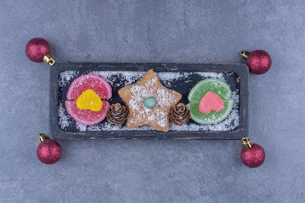 Une planche sombre avec des biscuits étoiles et des bonbons à la gelée sucrée