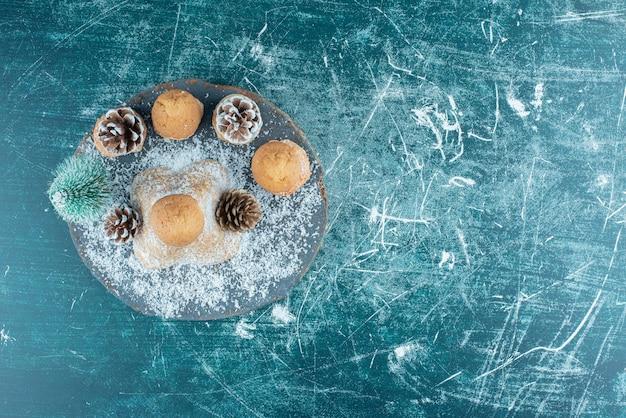 Une planche sombre en bois avec des petits gâteaux et des pommes de pin en poudre avec du sucre.
