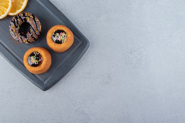 Planche sombre de délicieux beignets au chocolat et gâteaux à la gelée. photo de haute qualité