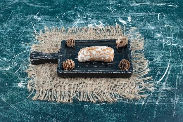 Une planche sombre avec du pain d'épice savoureux et des pommes de pin. photo de haute qualité