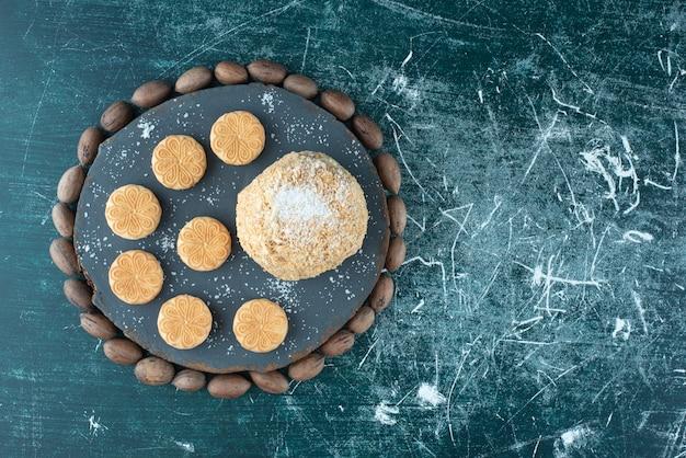 Une planche sombre avec des gâteaux et des biscuits sur un fond coloré. photo de haute qualité