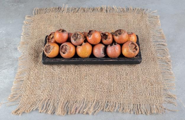 Une planche sombre avec des kakis frais et juteux sur un sac. photo de haute qualité