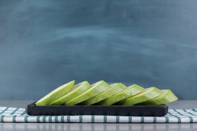 Une planche sombre avec des légumes de courgettes tranchés. photo de haute qualité