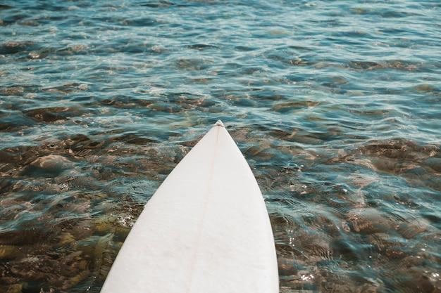Planche de surf couchée sur de l'eau propre