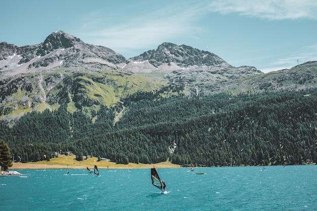 Planche à voile dans le paysage de montagne des alpes suisses avec l'herbe et la forêt de roches de lac turquoise