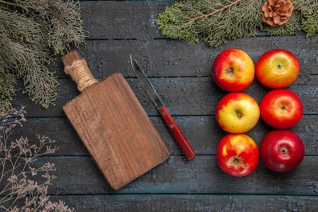 Planche vue de dessus et pommes six pommes à côté d'un couteau et d'une planche à découper en bois sous les branches avec des cônes
