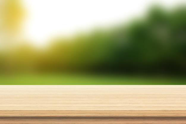 Plancher de bois avec des arbres flous de l'arrière-plan du parc naturel et de la saison estivale